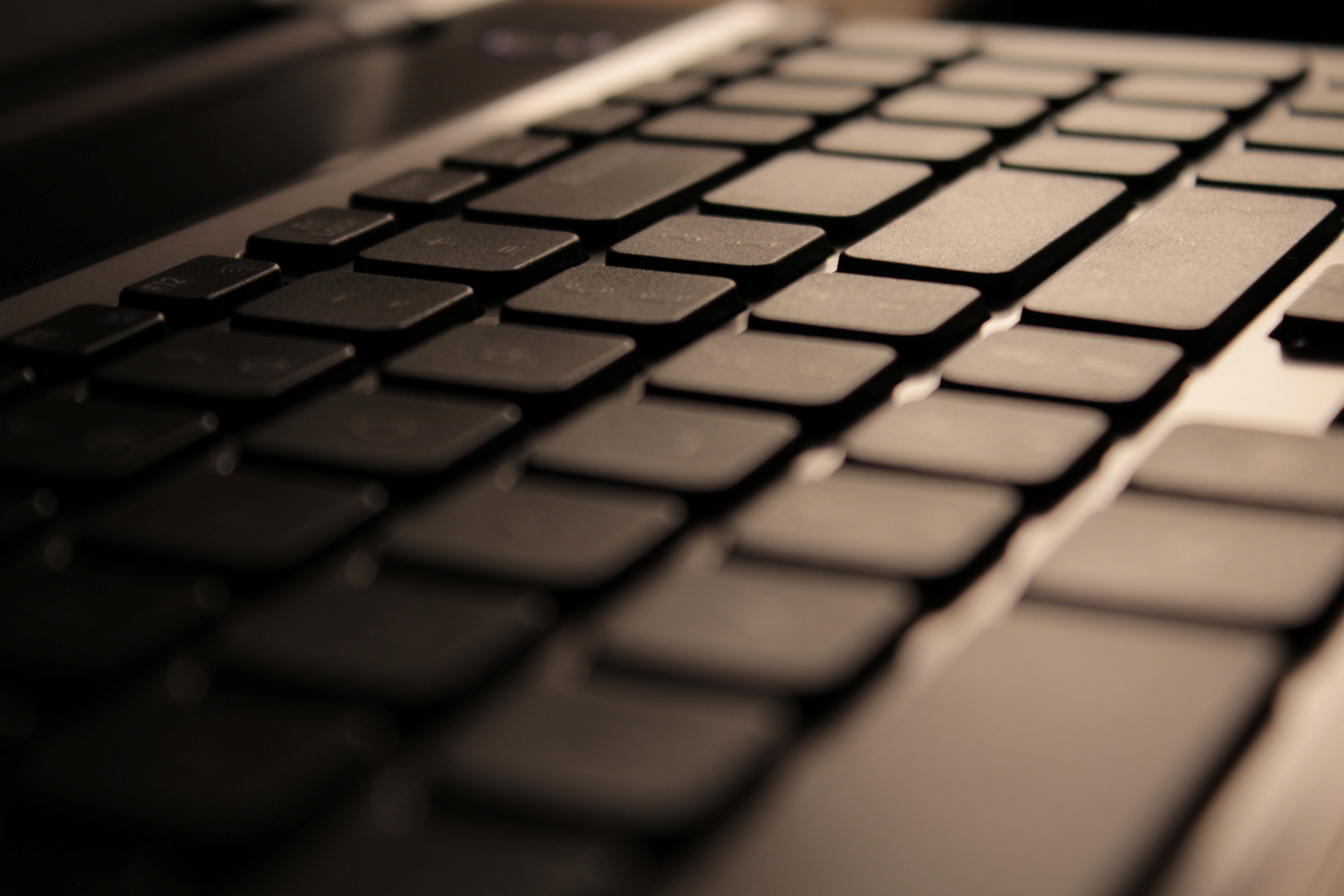 Classic laptop keyboard with black buttons shot in dark, warm scenery.